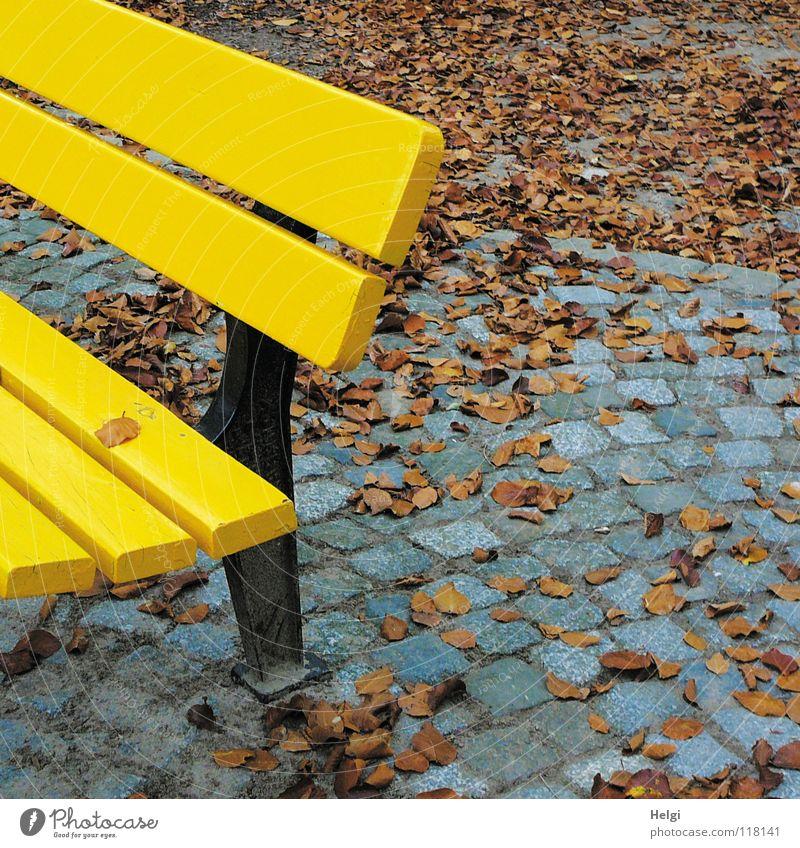 Teil einer gelben Bank auf Kopfsteinpflaster  mit Herbstlaub Park Parkbank pflastern Blatt fallen stehen Einsamkeit Zusammensein nebeneinander grau schwarz