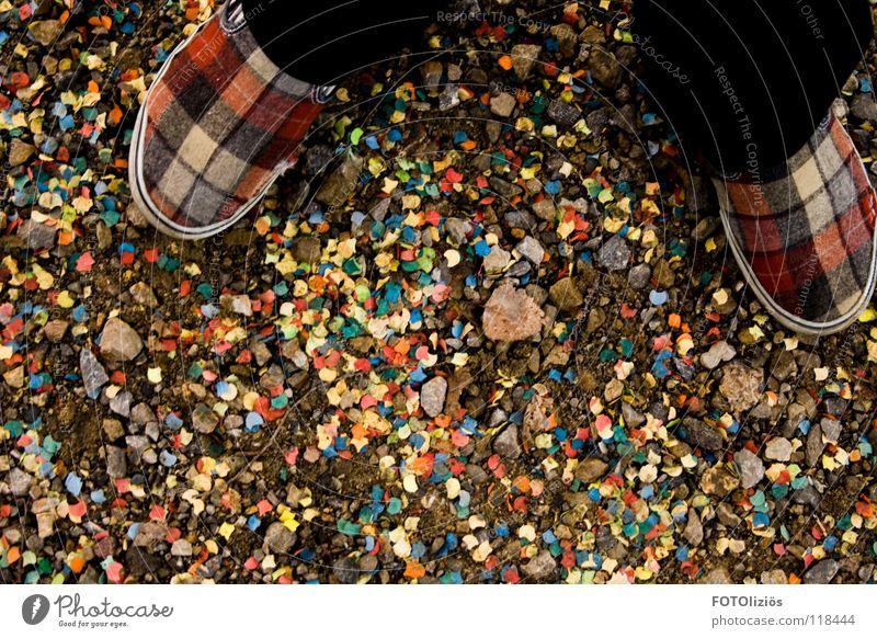 Restdeko vom Silvesterfest Konfetti Papier Schnipsel mehrfarbig Müll Party Schuhe Schottenmuster Hausschuhe Kies Geröll Fußweg Karneval kariert Filz