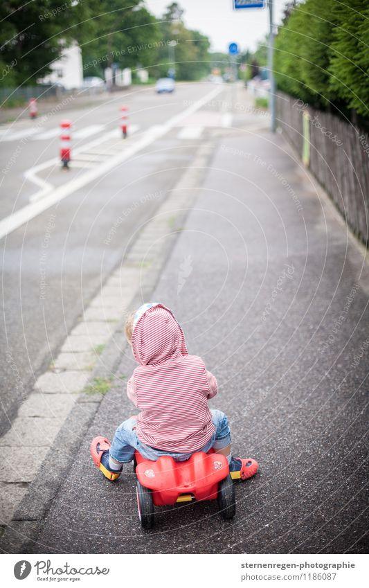 Straßenverkehr Bobbycar Kind Kindheitserinnerung Kleinkind PKW Bürgersteig Fußweg fahren Spielen rot Spielzeug Verkehrsleitkegel Pylon Kapuze