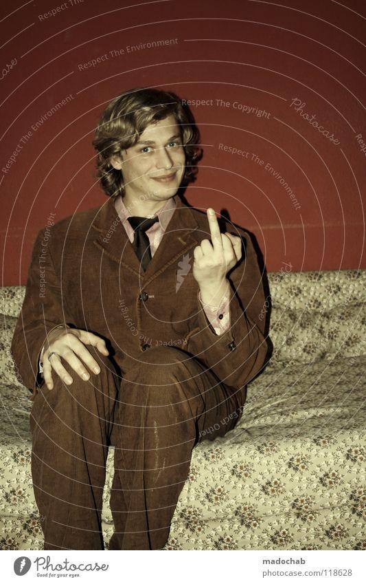 LAMM IM SCHAFSFELL Mittelfinger Stinkefinger Junger Mann 18-30 Jahre Anzug Krawatte schick unfreundlich frech provokant Sofa sitzen Blick in die Kamera