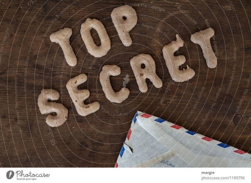 Die Buchstaben TOP SECRET mit einem Luftpos t- Briefumschlag auf einem rustikalen Holztisch Prüfung & Examen Büroarbeit Wirtschaft Industrie