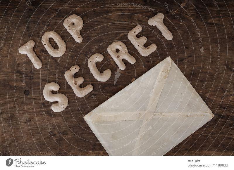 Die Buchstaben TOP SECRET mit einem Briefumschlag auf einem rustikalen Holztisch Prüfung & Examen Büroarbeit Arbeitsplatz Wirtschaft Industrie