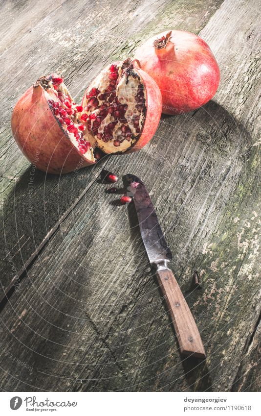 Granatapfel auf Holztisch Frucht Dessert Essen Vegetarische Ernährung Diät Saft Tisch alt dunkel frisch retro saftig rot Farbe hölzern Messer altehrwürdig
