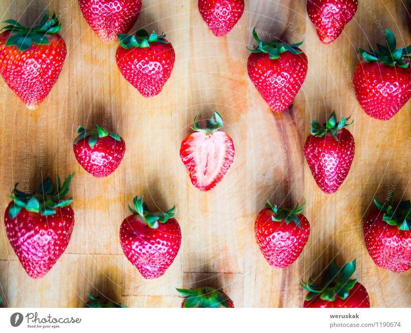 Eine geschnittene Erdbeere in einem vereinbarten Muster von Erdbeeren grün Sommer Einsamkeit rot natürlich Holz Gesundheit außergewöhnlich Frucht Design