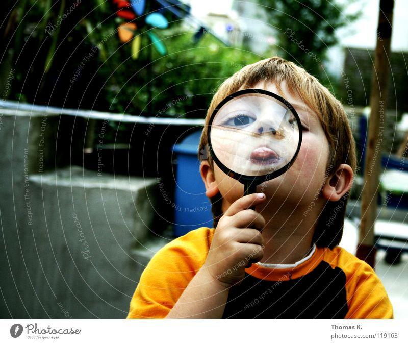 Through The Looking Glass III Kind Junge vergrößert Hand Brille suspekt Porträt untersuchen Nationale Sicherheit Spuren lesen Suche Suchprogramm finden