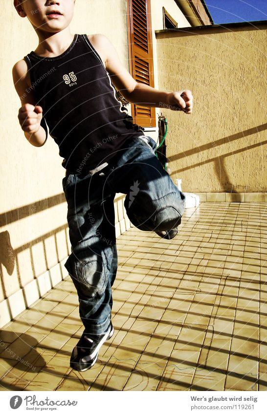 Hüpf hüpf Kind blau Freude Spielen Junge springen Mauer Luft Metall hell braun fliegen Streifen Ziffern & Zahlen Jeanshose Schönes Wetter