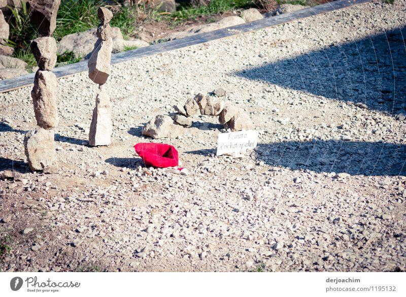 Ein  Roter Hut liegt auf dem Weg auf dem  mit Steinen Weg. Bitte um eine Geld Spende. Steinhäufchen gestappelt stehen dabei. Freude Leben betteln ansammeln