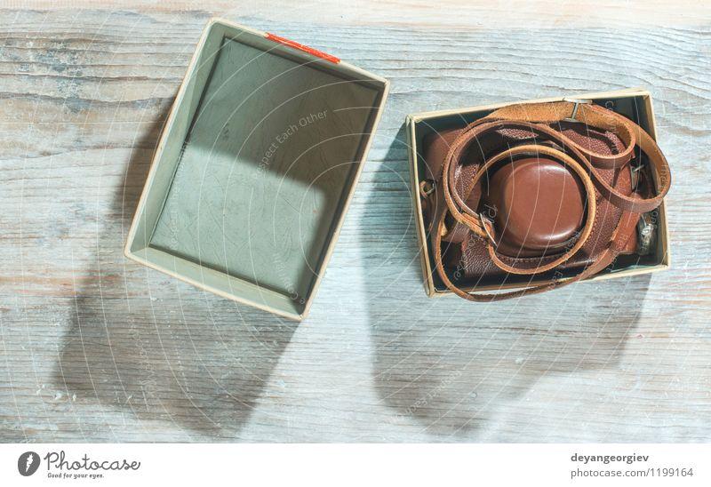 Weinlesefotokamera auf weißem hölzernem Hintergrund alt schwarz Stil braun Tisch Kreativität Aussicht Fotografie retro Grafik u. Illustration Fotokamera
