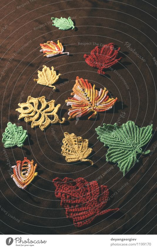Gestrickte Herbstblätter auf braunem Textil Natur schön rot Blatt gelb Glück Jahreszeiten Hut Pullover November Wolle Oktober stricken Erntedankfest