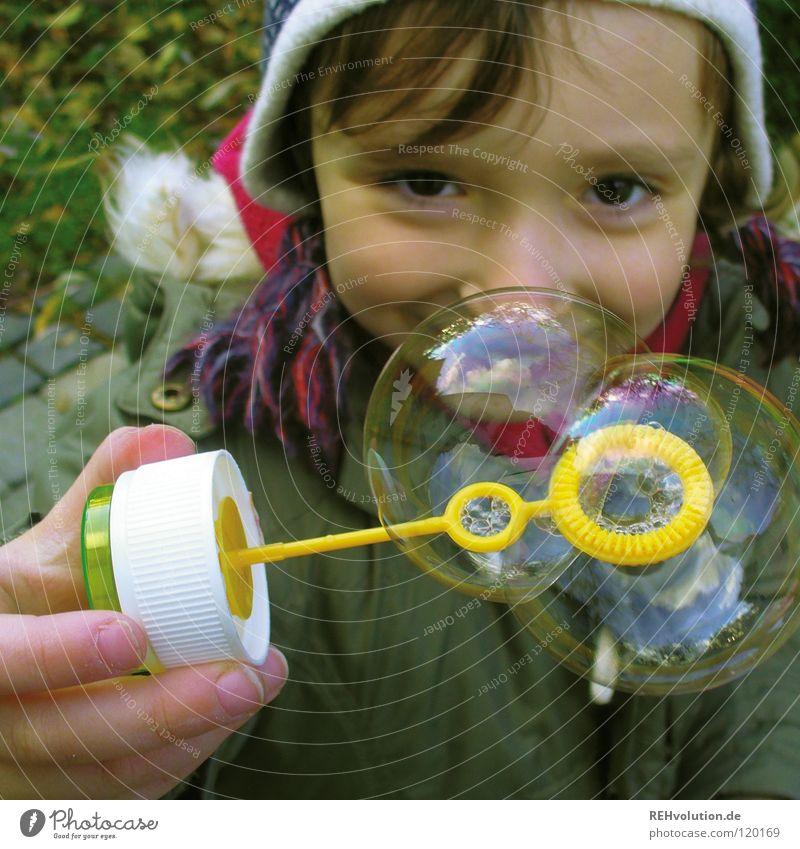 Guck ma! Kind Spielen Kleinkind Kindergarten Seifenblase Verschmitzt Junge kalt Winter grün Mütze blasen klein süß Freude Blick Beleuchtung Auge Garten Soap