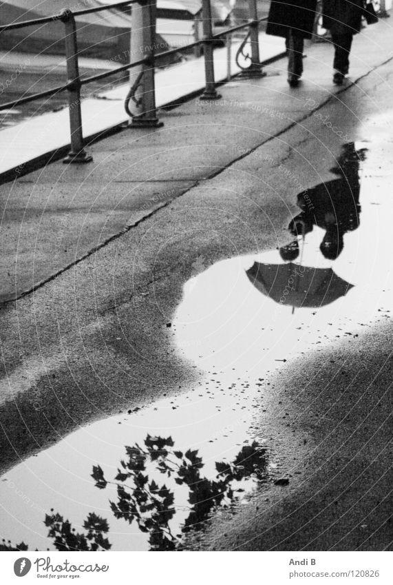 Spazieren im Regen Spaziergang Pfütze Frau Reflexion & Spiegelung zwei Menschen Schwarzweißfoto Reflexionen im Wasser Traurigkeit