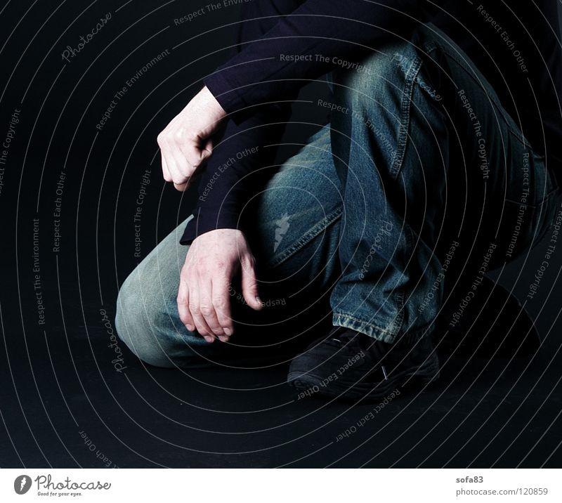 dackelperspektive Mann schwarz Beine Arme Bekleidung Coolness Jeanshose Körperhaltung lässig Knie Hockstellung