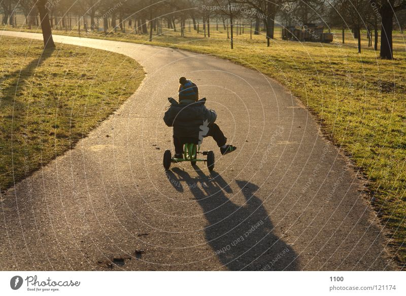 Der Sonne entgegen Dreirad Fahrer Kind Abendsonne Sonnenuntergang Fahrzeug Verkehrsmittel Schuhe Muskulatur Junge Straße Wege & Pfade Baumwiese Bübchen Schatten