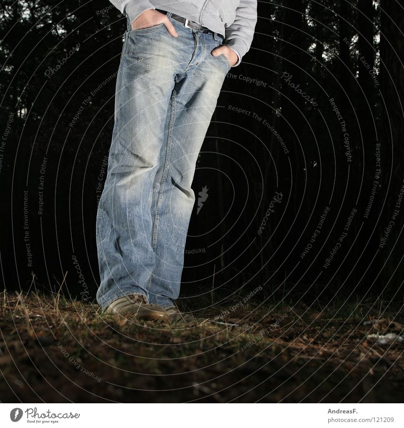 Waldmeister Mann Hand dunkel Schuhe Beine Beleuchtung warten Bekleidung Jeanshose stehen Hose Waldboden Ungeduld Hosentasche