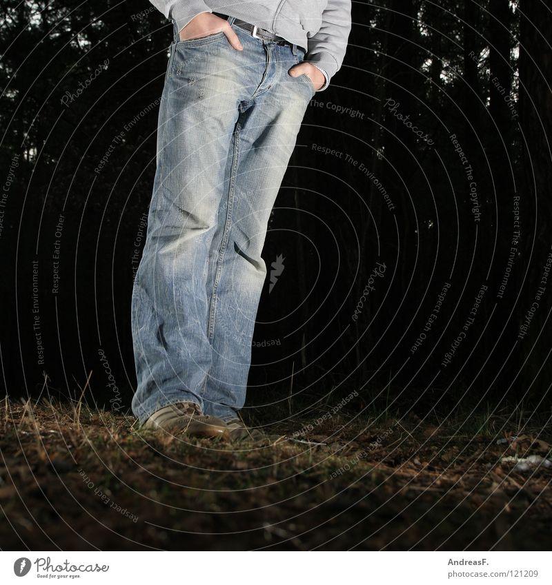 Waldmeister Mann Hand Wald dunkel Schuhe Beine Beleuchtung warten Bekleidung Jeanshose stehen Hose Waldboden Ungeduld Hosentasche