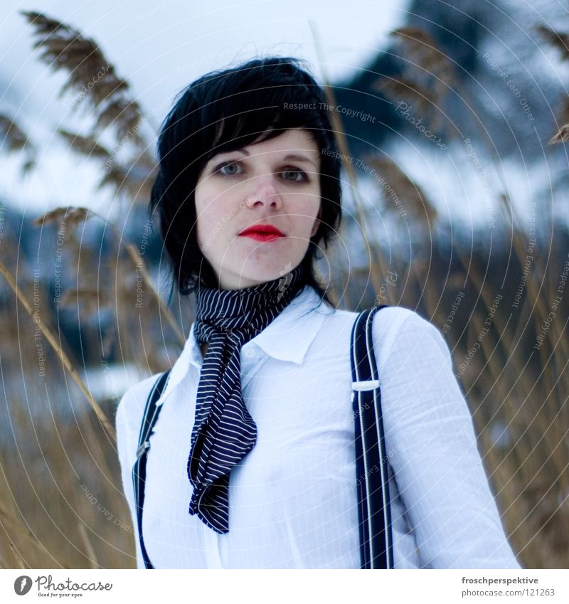 schau mich nicht so an Frau Schminke geschminkt schwarzhaarig Märchen Hosenträger Tanne Schweiz Schilfrohr Winter kalt graue Wolken See frieren Blick skeptisch