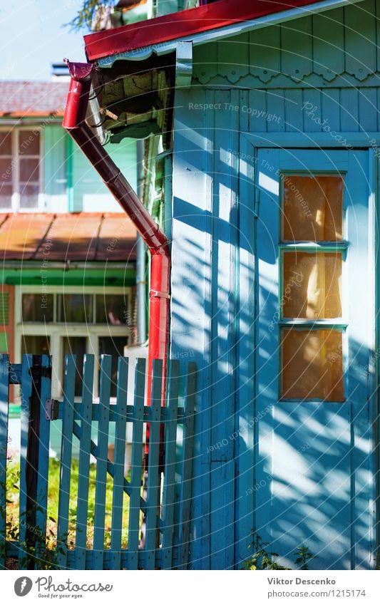 Hell gefärbtes Haus des Sommers mit einem Tor an einem sonnigen Sommertag Ferien & Urlaub & Reisen alt blau Pflanze schön grün Farbe weiß Blume rot gelb Straße