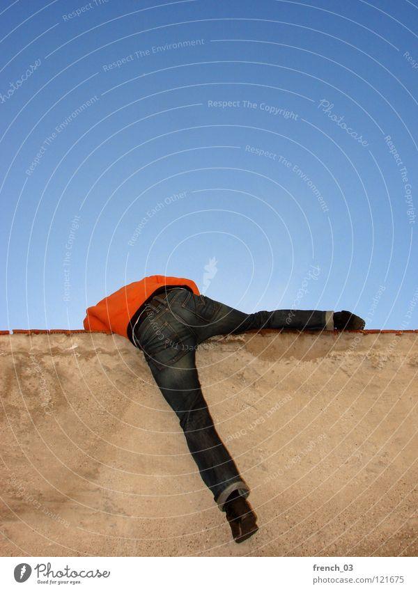 Gleich bist du frei Mauer Wand Mann gelb rot Gegenlicht zyan himmelblau Schuhe Hose Pullover Ausbruch driften oben gefangen einsperren eng eingeengt befreien
