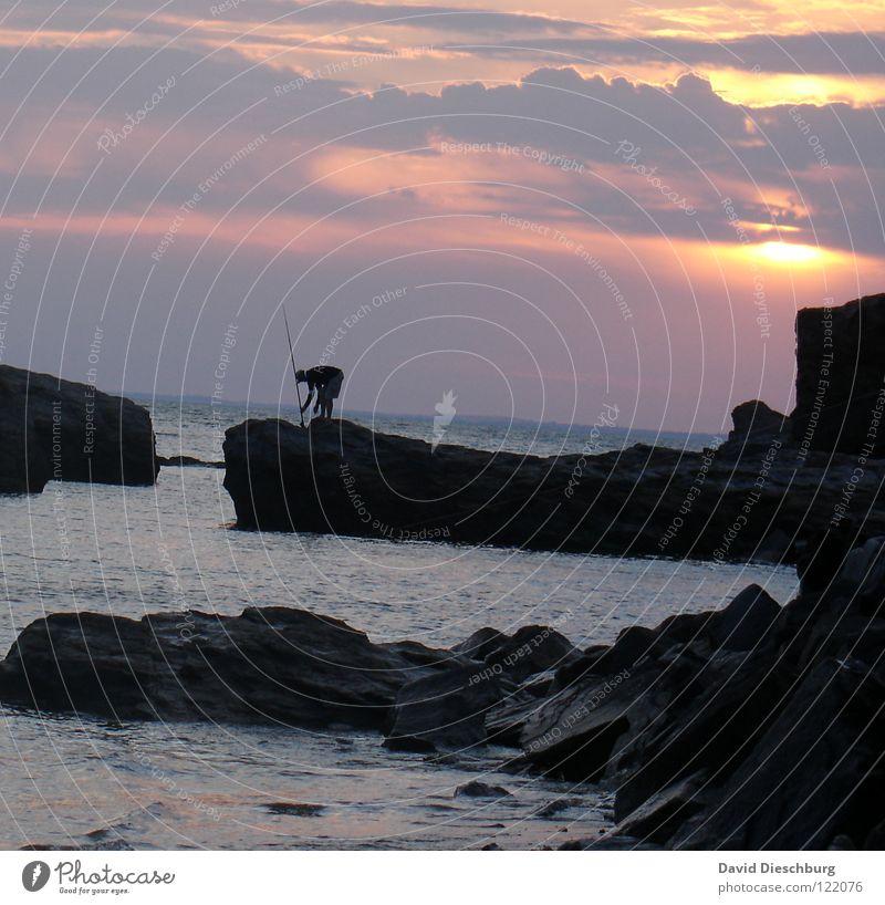 The lonely angler #I Wasser Himmel Sonne Meer blau Sommer Strand Ferien & Urlaub & Reisen schwarz Wolken Einsamkeit gelb Berge u. Gebirge Stein Sand hell