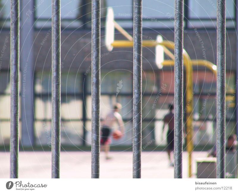 Eingesperrt Spielen Sport Schulhof Gitter Basketballkorb Schule Zaun gefangen tribbeln Farbfoto mehrfarbig Außenaufnahme Tag Unschärfe Schwache Tiefenschärfe