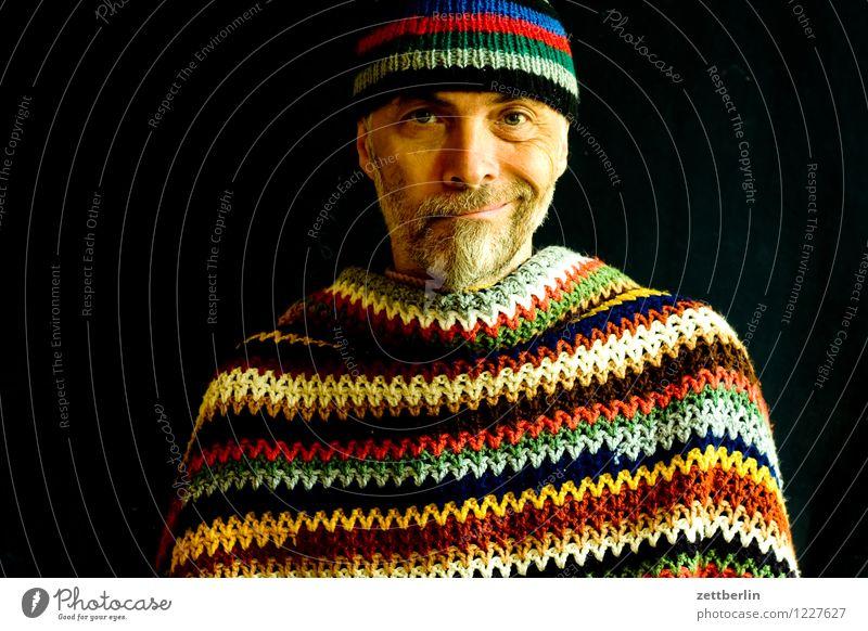 Mann mit gestrickter Wollmütze und gehäkelter Wolldecke Mensch Erwachsene Senior Porträt Gesicht mehrfarbig Muster Streifen Umhang Pullover Mütze Wärme Bart