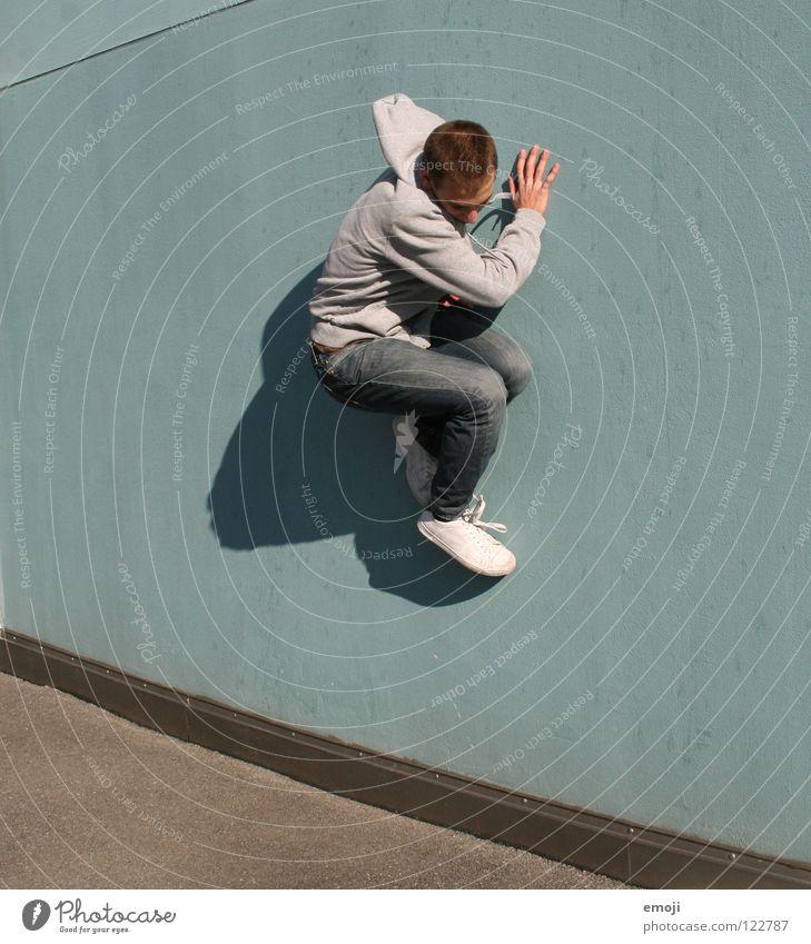*kleb Mann Wand gehen springen hüpfen Barriere türkis Mensch Wut Aggression Ärger kleben Luzern modern Spielen hochgehen man young sportlich Dynamik Bewegung