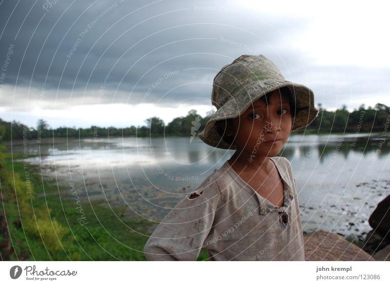 Ruhe vor dem Sturm Kind Wasser Mädchen ruhig Traurigkeit Regen Arme Armut Neugier Fluss Sehnsucht Asien Hut Sturm Denkmal Wahrzeichen