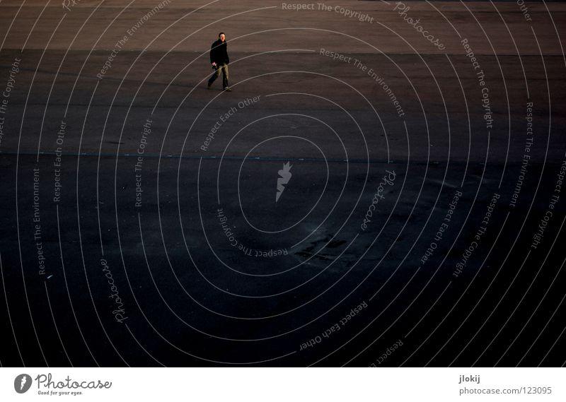 Alone Platz Macht winzig groß klein Beton Mann maskulin gehen Spaziergang unten Pfütze Fotograf Hose Jacke Winter kalt braun schwarz dunkel Ferne Stadt Park