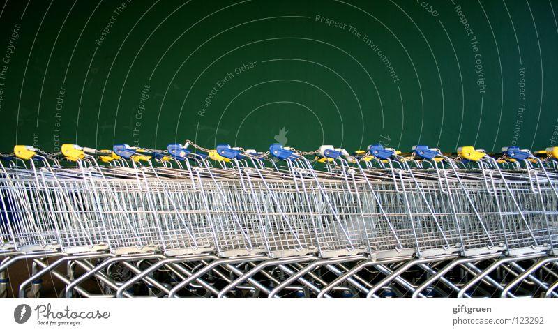 fuhrpark grün Wand Metall viele Reihe Markt Supermarkt Konsum Einkaufswagen Wagen Behälter u. Gefäße aufgereiht Reihenfolge hintereinander konsumgeil