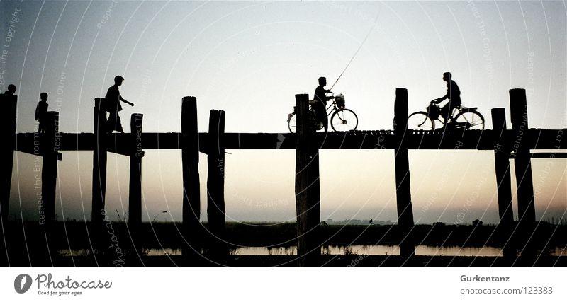 Abends in Myanmar Mensch Wasser Holz See Fahrrad Verkehr Brücke Asien Verbindung Schatten Silhouette Abenddämmerung Pfosten Myanmar Teak