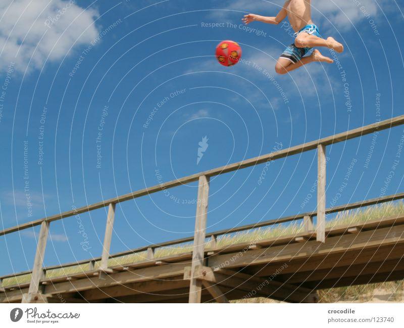engelsfußball Sylt Strand Steg Hose schießen Spielen springen Luft Schweben kopflos Wolken Froschperspektive rot Freude Funsport Ball fallen Bewegung Sand Arme