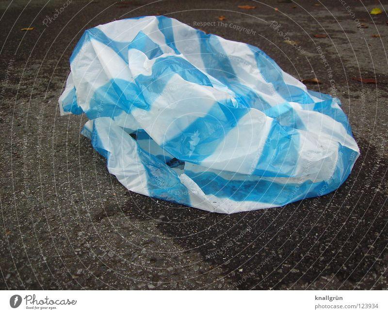 Liegengeblieben dunkel hell liegen Asphalt Müll Streifen Statue obskur Falte gestreift Plastiktüte blau-weiß Restmüll