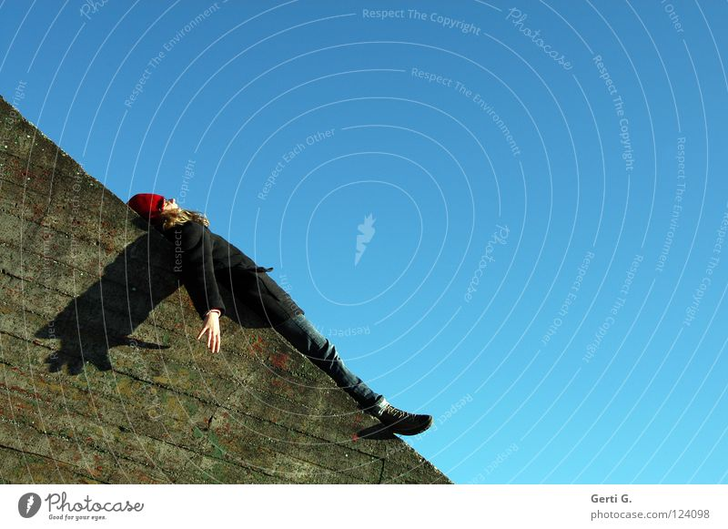 chilln Mensch Hand Jugendliche Himmel blau Erholung Stein Mauer Zufriedenheit Arme verrückt Engel Jeanshose liegen Flügel Hut