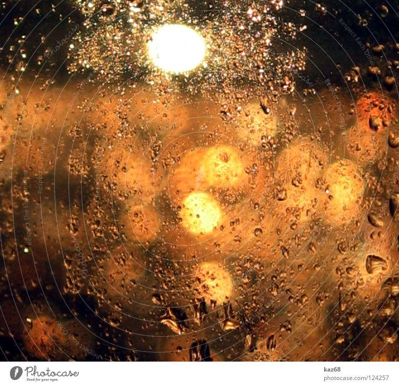 Goldregen Wassertropfen Fenster nass feucht reich Hintergrundbild Licht gelb rot glänzend Regen Fensterscheibe Lichtschein Niederschlag Lichtfleck durchleuchtet