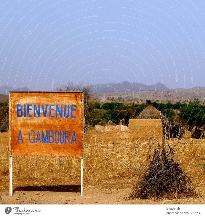Welcome to Gamboura (Kamerun) Berge u. Gebirge braun Armut Afrika Dorf Hütte Hinweisschild Steppe Willkommen Straßennamenschild Warnschild