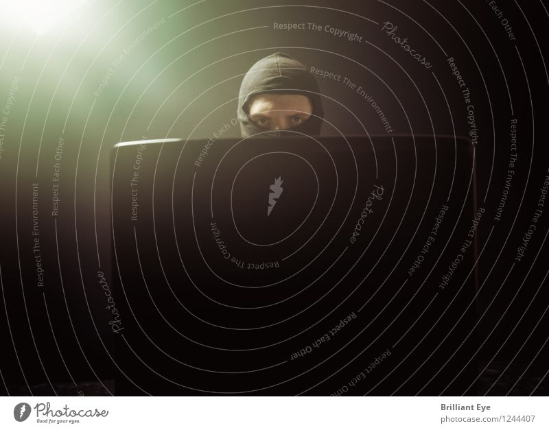 Finster dreinblickender Maskenmann vor Laptop Mensch Mann dunkel schwarz Erwachsene Gefühle Stimmung hell Business maskulin gefährlich Computer bedrohlich Macht