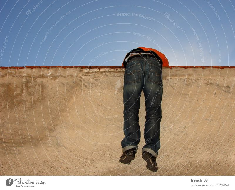 Auf der Mauer... Wand Mann gelb rot Gegenlicht zyan himmelblau Schuhe Hose Pullover Ausbruch driften oben gefangen einsperren eng eingeengt frei befreien