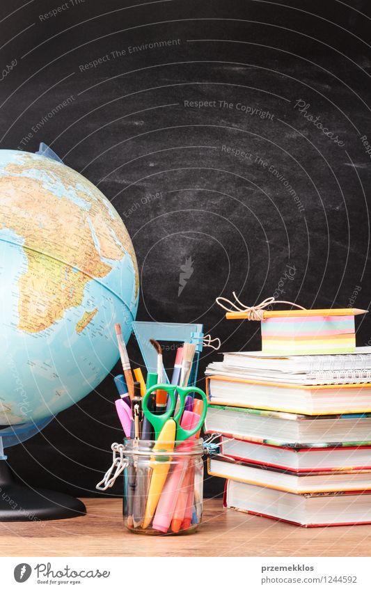 Schulzubehör mit Tafel im Hintergrund Schreibtisch Schule lernen Arbeitsplatz Werkzeug Schere Waage Buch Erde Schreibstift Globus schwarz Bildung blanko