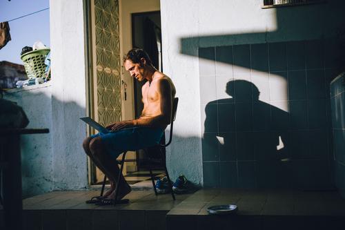 Junger Mann mit Laptop auf dem Schoß Lifestyle Ferien & Urlaub & Reisen Ausflug Abenteuer Ferne Städtereise Sommer Häusliches Leben Wohnung Haus Stuhl