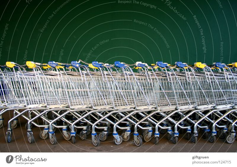 in reih und glied Einkaufswagen Metall grün Supermarkt Wand Konsum Behälter u. Gefäße Reihe aufgereiht Strukturen & Formen hintereinander viele Menschenleer