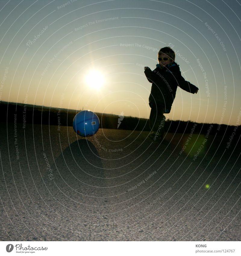 wir sind torsten frings Kind Spielen Gegenlicht Fußball Sonnenbrille Asphalt halbdunkel Freude Kleinkind Ballsport child play mit dem fuß Straße cool kid