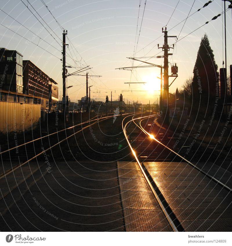 Ankunft bei Sonnenuntergang Gleise Eisenbahn Bahnübergang Elektrizität Haus Baum Licht Gegenlicht Bahnhof Verkehr Himmel Verbindung Abend Straße Leitung
