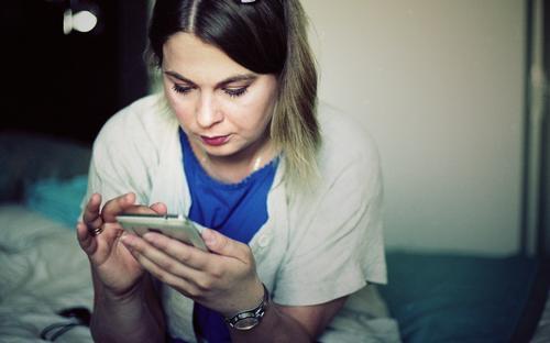 Nachricht von Kamlia Telekommunikation PDA Junge Frau Jugendliche 18-30 Jahre Erwachsene Accessoire blond Bettwäsche Raum Hotelzimmer Kommunizieren schreiben