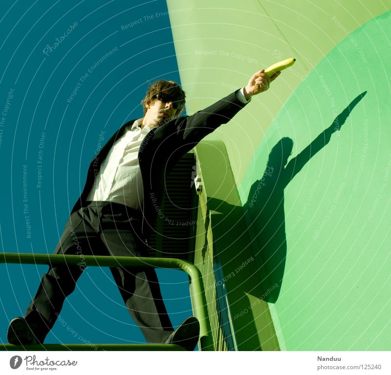 : R E L O A D E D : shot Agent Anzug Mann Sonnenbrille maskulin grün Matrix schießen Kerl Banane Wand zielen Körperhaltung Gewalt brutal böse Bösewicht