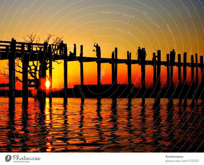 Birmanische Brücke Mensch Wasser Baum Sonne rot Holz See Brücke Asien Abenddämmerung Pfosten Myanmar Teak Mandalay Holzbrücke
