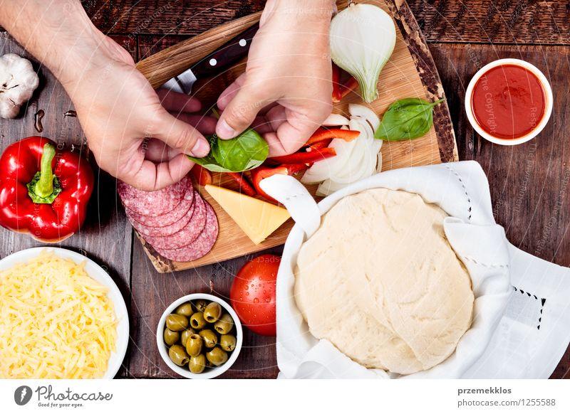 Vorbereiten der Zutaten für hausgemachte Pizza Lebensmittel Käse Gemüse Abendessen Fastfood Schalen & Schüsseln Tisch Hand 1 Mensch Blatt frisch Basilikum