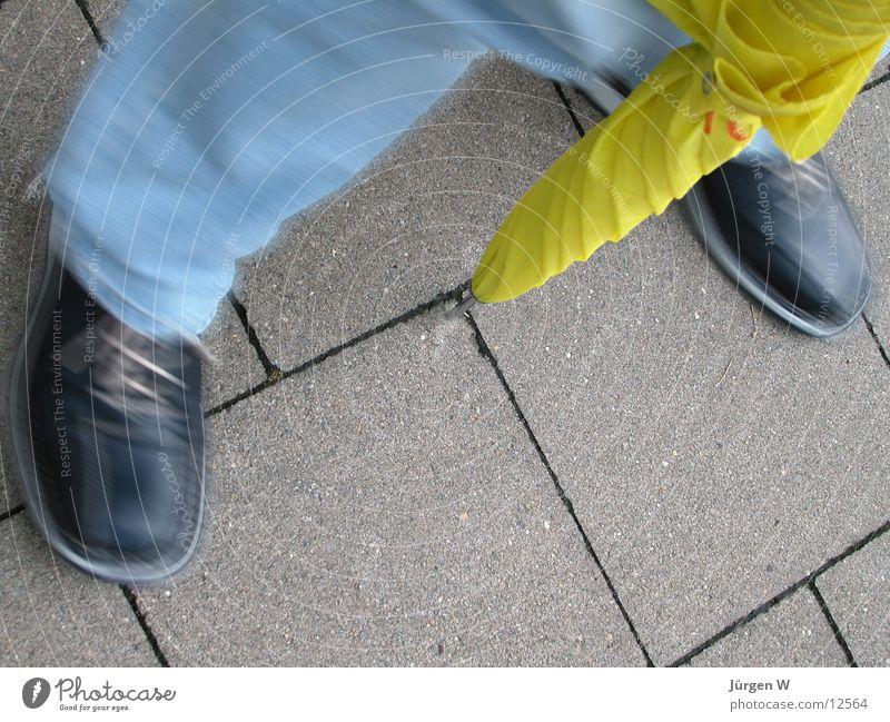 mit Schwung Mensch gelb Schuhe Beine Jeanshose Regenschirm