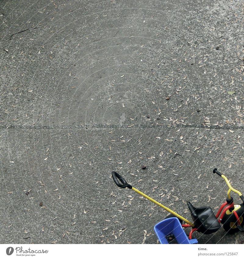 Lukas kommt gleich wieder Beton Bodenbelag Spielplatz Kinderfahrrad Spielzeug rot gelb Parkplatz Blatt Herbst Verkehr Innenhof blau Sitzgelegenheit
