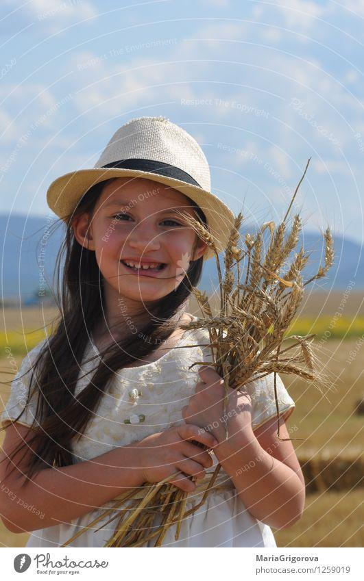 lächelndes kleines Mädchen, das Weizen in den Händen hält Lebensmittel Getreide Bioprodukte Lifestyle schön Gesundheit Sommer Sonne Mensch Kind Körper Kopf