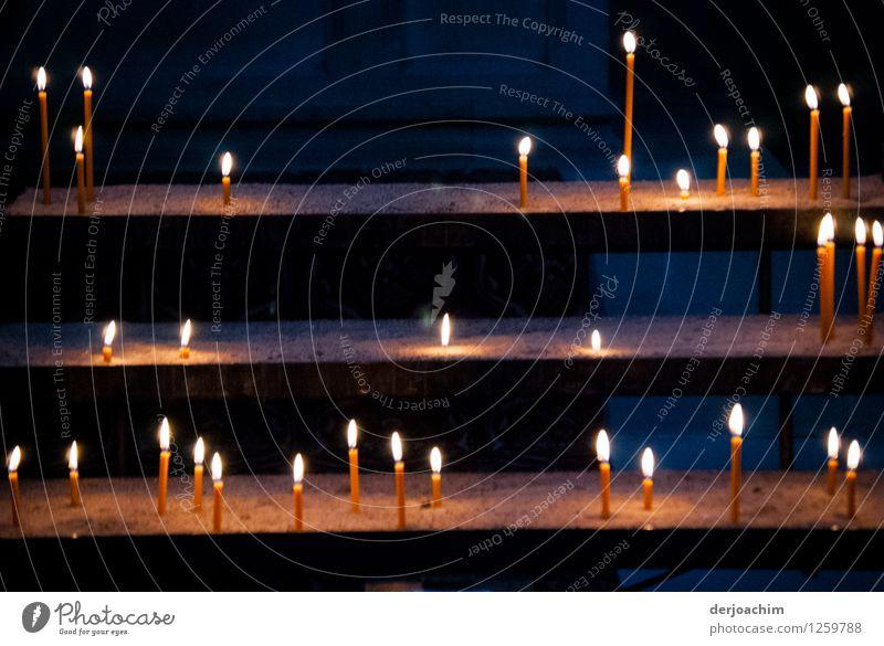 Thementag:vielfältig/Kerzenschein, Kerzenopferstock in einer Kirche. Ganz viele Kerzen stehen auf einer abgestuften Treppe. Mit dunklem Hintergrund. exotisch